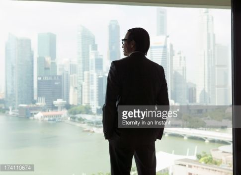 Stock Photo : Asian businessman looking out of window at city