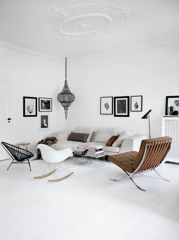 white with black accents and some classic iconic chairs in this scandinavian space.