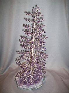 This stately Spruce design features graduated layers of branches with geniune Amethyst leaves affixed to tarnish resistant silver craft wire. The