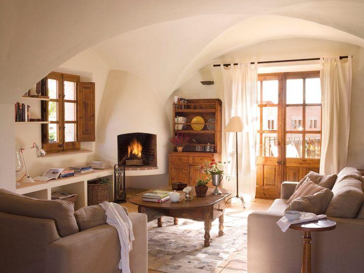 Muy cálido y con muebles de obra  Salón con sofá tapizado con tela de Pepe Peñalver, comprado en El Taller dels Somnis. Alfombra de piel de vaca, de Última Parada. Pavimento de terracota, de Cerámicas Raventós.