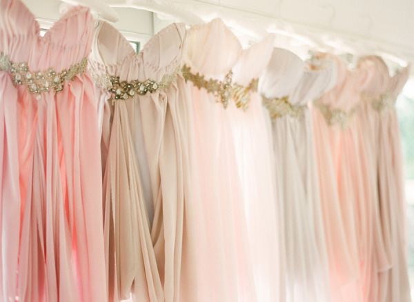 Bridesmaid dresses in different soft colors and sparkly belts.