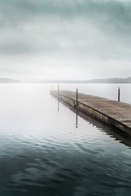 To the other side, by photographer Jan Bedoire. Wooden pier going into the foggy lake. Available as poster and laminated picture at printler.com, the marketplace for photo art.