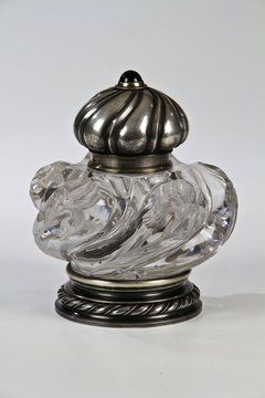 A Fabergé glass and silver inkwell stand. The spherical inkwell with hinged silver cover and finial applied with an amethyst cabochon. Gilt interior. The glass body finely engraved with lilies. The silver-mounted foot gadrooned.