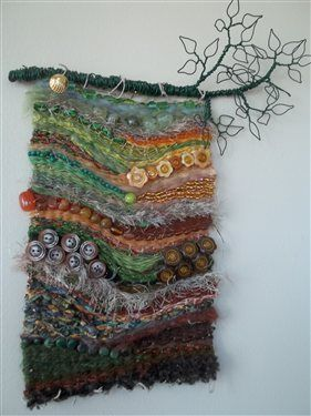 Wire, fabric strips, ribbon, yarn, buttons, beads woven into wall hanging.
