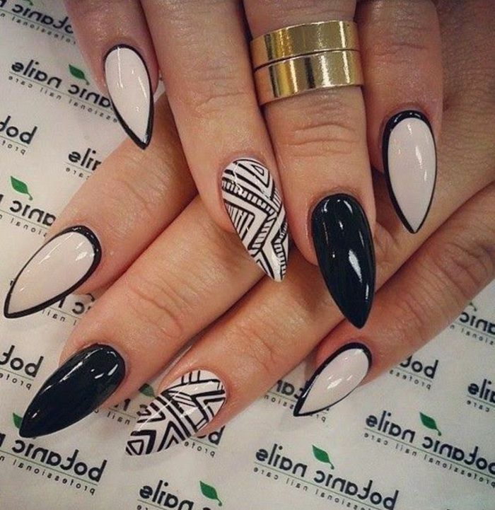 contasting white and black stiletto nails, black hand drawn details, and frame effect, on two hands, with solid gold rings