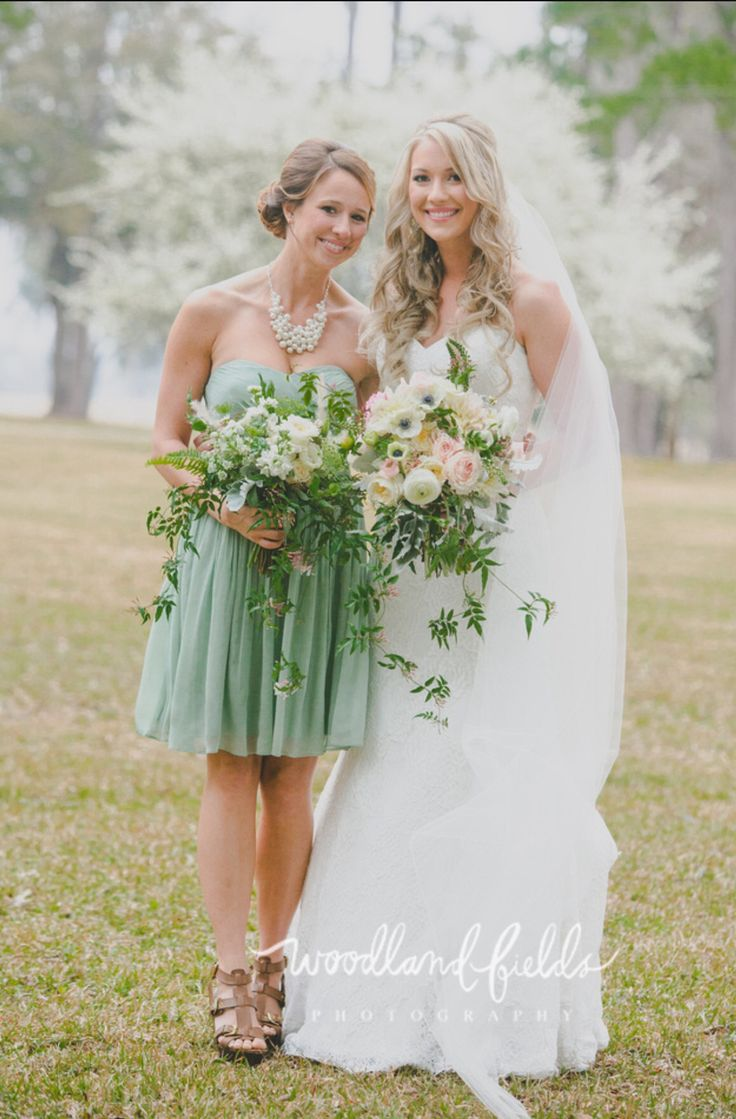 the bride and her bridesmaid show off their bouquets. bride carries bouquet  of kiera garden roses, light pink ranunculus, white ranunculus, white veronica, white anemone, patience garden roses, cafe au lait dahlia, jasmine trails, dusty miller, fern & greenery wrapped in green gingham check ribbon and the bridesmaid carries a bouquet of vendela roses, white stock, white lisianthus, white queen anne's lace, seeded eucalyptus, dusty miller, fern, jasmine trails, white fountain grass…