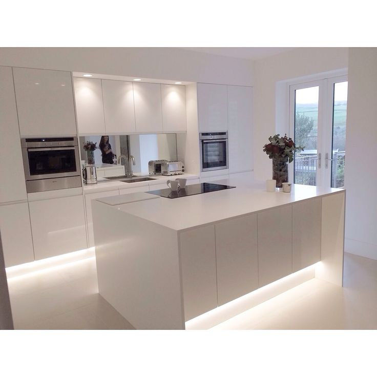 Modern white gloss integrated handle kitchen with 18mm Corian wrap and worktops. Design by HollyAnna.