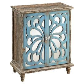 """2-door cabinet with cutout overlay and a weathered finish.   Product: CabinetConstruction Material: Wood and mirrored glassColor: Weathered brown and blueFeatures:  Lovely patina and trimDecorative knobs add sparkleTwo doors and one interior shelf Dimensions: 31.25"""" H x 26"""" W x 13"""" D"""