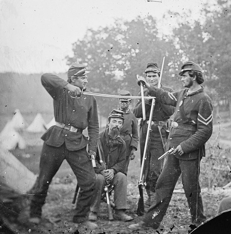 Two Union soldiers pose having a mock sword and gun fight in a camp, c. 1863