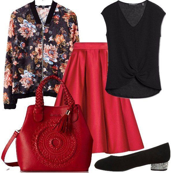 Outfit formato da una gonna ampia a campana in raso rosso, una t-shirt con nodo in nero e un bomber con stampa floreale. Il look si completa con una borsa a mano in fintapelle rossa e un paio di scarpe nere con tacco tempestato di pietre brillanti.