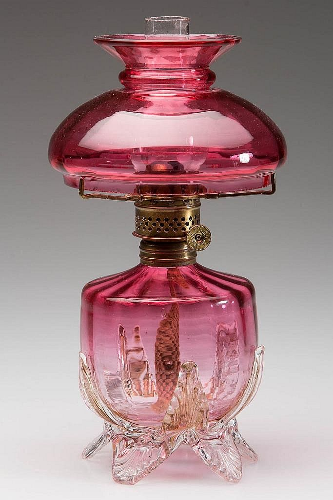 "PANEL-OPTIC VICTORIAN CRANBERRY GLASS MINIATURE LAMP, cranberry glass, colorless applied leaves and feet to base, matching umbrella shade. Period burner and tripod,  8"" H,  Fourth quarter 19th/early 20th century / SOLD $575"