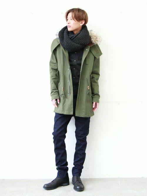 オリーブグリーンのモッズコートにグレーのスヌード、ネイビーパンツ、黒のブーツをあわせて着こなす男性