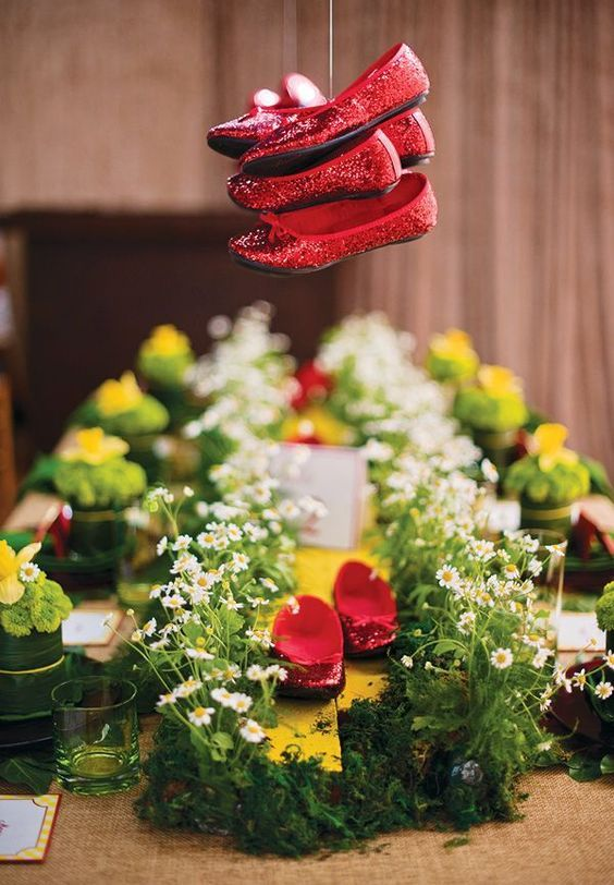 Wizard of Oz party idea > ruby red shoes centerpiece. The hanging shoes are the star of this tablescape.