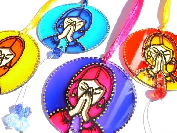 Namaskara Mudra Mudra é caracterizado como gesto, posicionamento místico das mãos. Essas posturas simbólicas dos dedos ou do corpo podem representar plasticamente determinados estados ou processos da consciência.  Namaskara Mudra é o gesto da oração.  Amuleto em acrílico com 6cm de diâmetro pintado à mão com técnica vitral e preso a uma fita de cetim colorida. Possui pedras acrílicas complementando a peça. Diversas cores.  O acrílico é um material 100% reciclável.  Sugestão de uso…