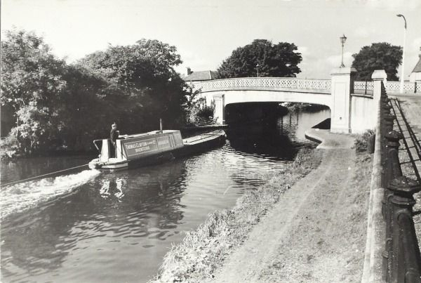 """Caption: """"View of a large timber yard alongside the canal at Southall, also of Thomas Clayton (Oldbury) Ltds tug 'Harken' towing a loaded barge near bridge 201 and passing a horsedrawn barge travelling away from the bridge"""""""