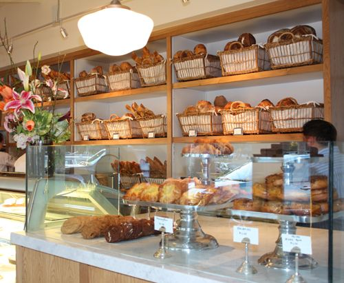 Love the bread basket idea behind the counter.    I like the glass with the countertop for display instead of a display case!