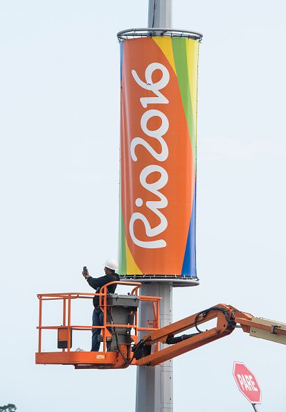 #RIO2016 A worker on a mobile lift holds up his mobile phone near a logo of the Rio 2016 Olympic Games in Rio de Janeiro on August 3 2016 / AFP / John...