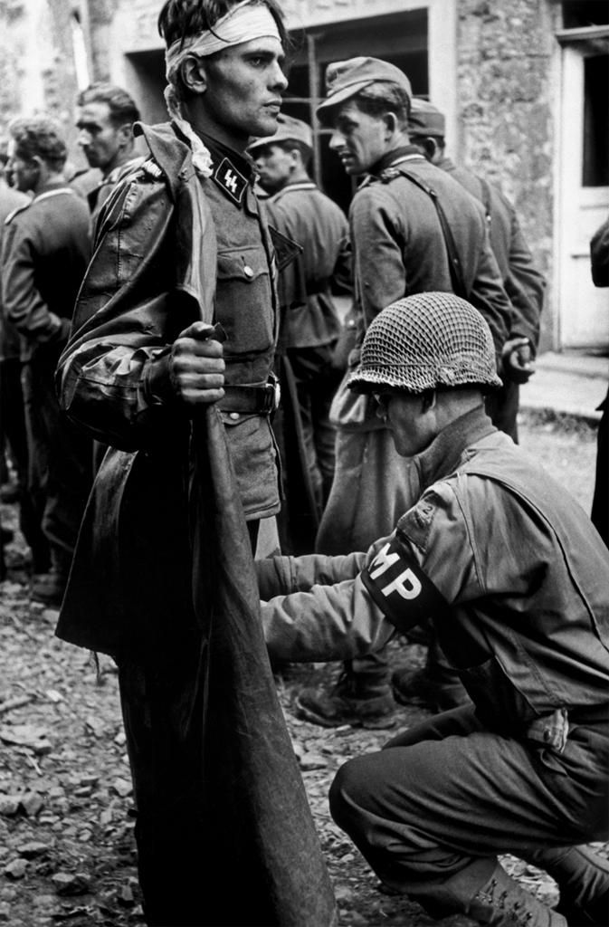 operationbarbarossa:  An American military policeman searching a captured German SS soldier - 1944  Photo by Robert Capa