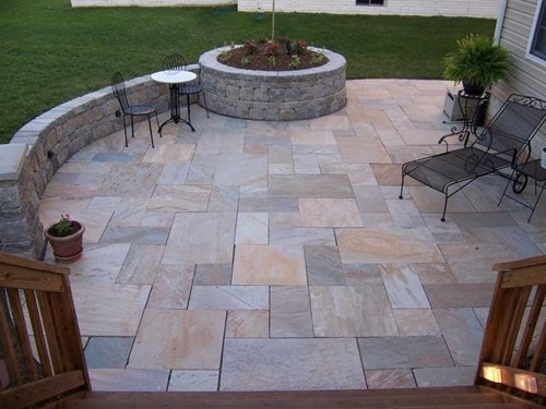 Geometric random stone patio with curved wall bench and for Curved garden wall ideas