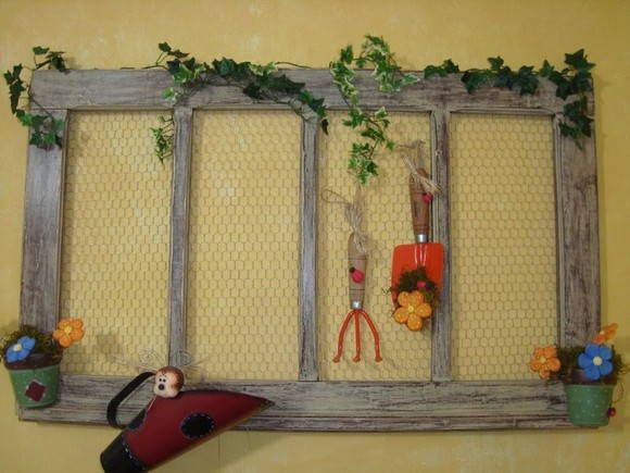 Janela decorada com joaninhas de biscuit country com vasinhos em ceramica e tela contem apretrechos de jardim.