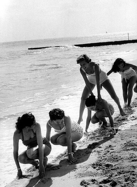 Models playing leapfrog on the beach in Miami, Florida, 1956. Photo by Lisa Larsen.