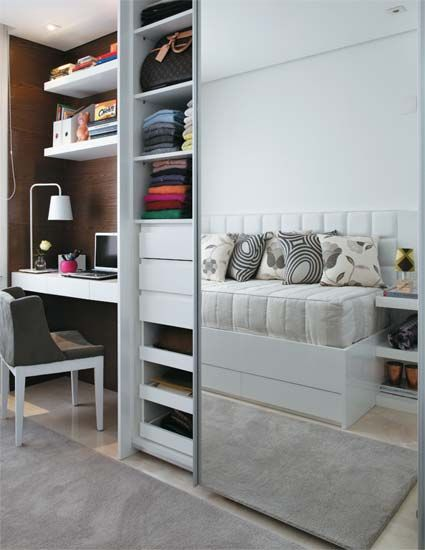 Built in desk with wall shelving above is flanked by Ikea Pax style wardrobe with mirrored doors. Reflected in the mirror is Ikea twin bed with under storage doors. An upholstered wall mounted headboard (side board) and a row of pillows give this single twinbed the look and function of a couch.