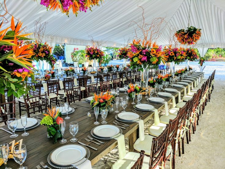 It is a incredible elaborated tropical Beach Reception Decor, nicely done with bird of paradise, sunflowers, two color or-quids, tropical foliage, tall center pieces accompanied by little ones and a rectangular vintage long tables and mahogany chiaviari chairs. Just stunning.