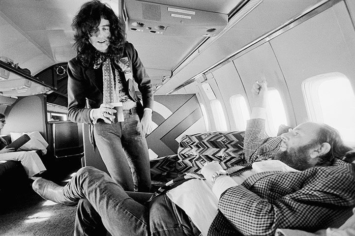 "Jimmy Page talks with the band's manager Peter Grant – the relationship between the two of them was crucial to Zeppelin's success – aboard the band's private jet, known as ""the starship""."