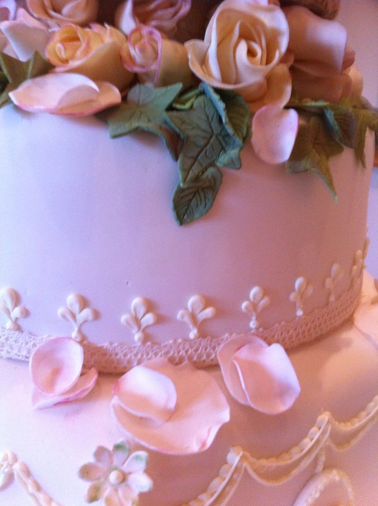 Eleanor, a five tier cake with a hexagonal cake at the bottom and delicate handmade roses and falling petals