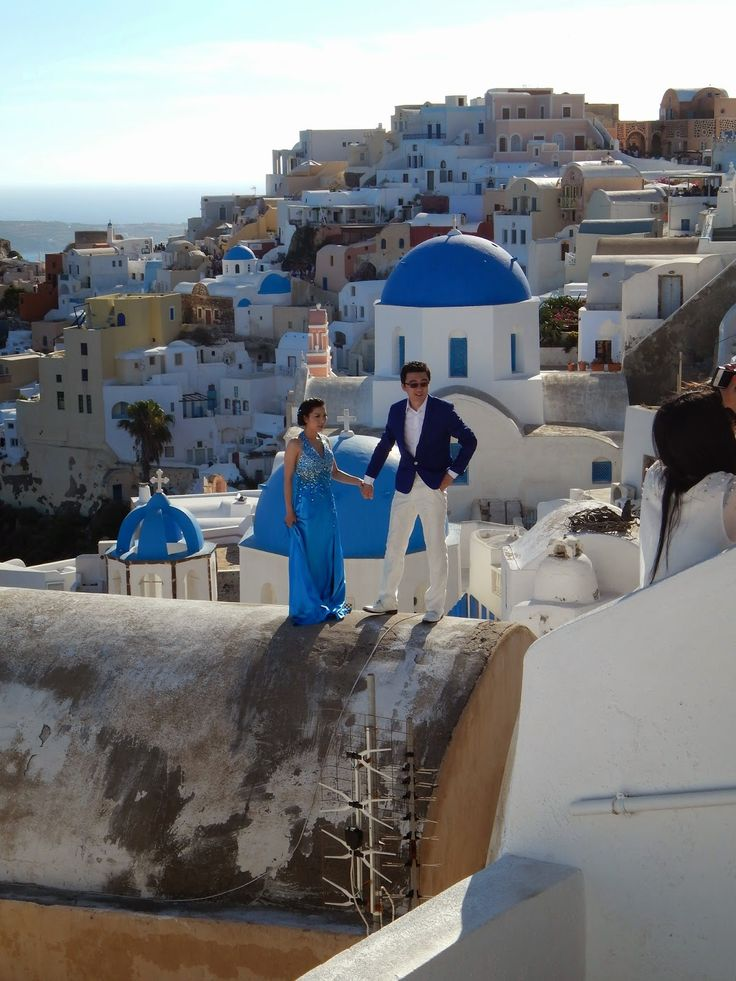 A couple in love possing on a rooftop in Oia village, Santorini island, Greece - selected by www.oiamansion.com