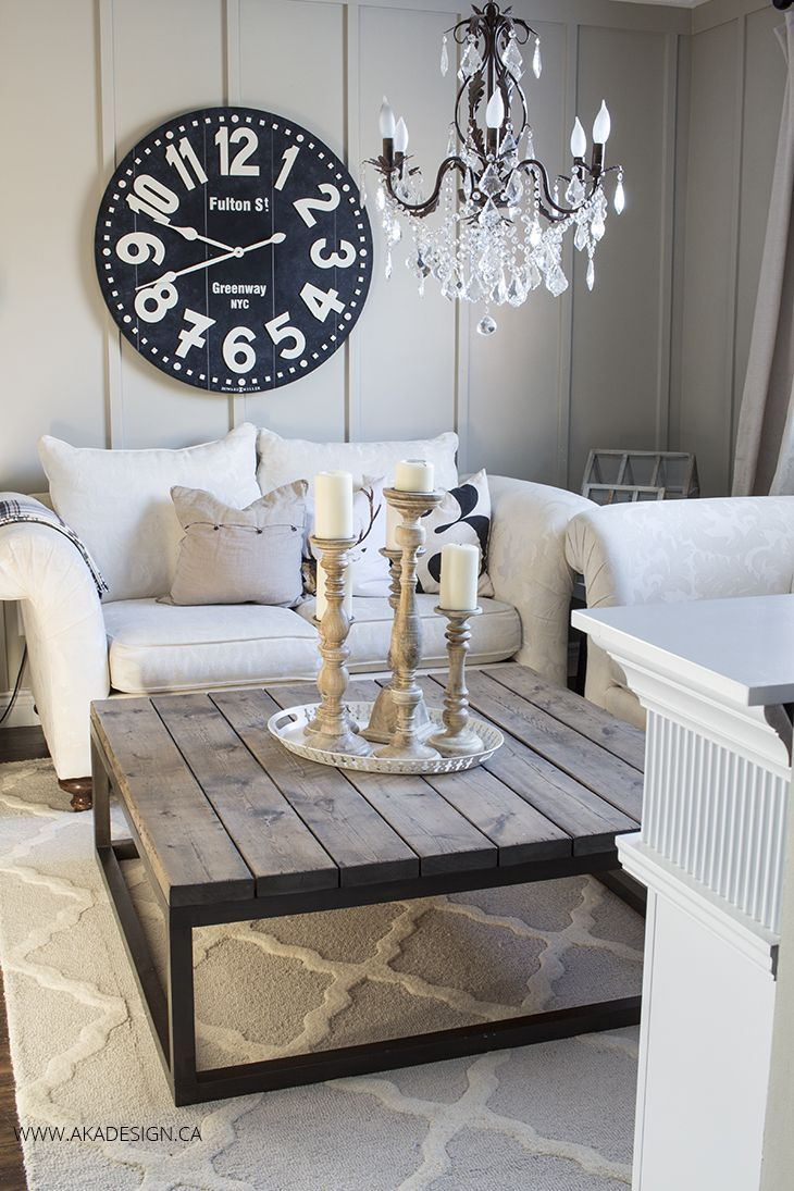 Living Room decor - rustic farmhouse style with board and batten walls, rustic planked coffee table with metal frame, crystal chandelier adds some glam, rolled armed cream colored sofas and trellis patterned cream and white rug | aka design