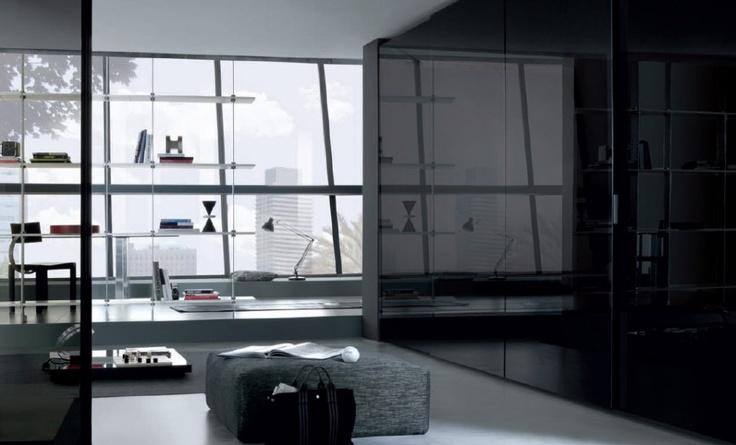 Glossy Black Sliding Door Wardrobe And Grey Ottoman Above White Flooring