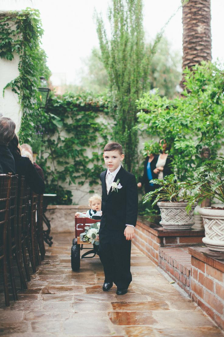 Ring bearer pulling a wagon with infant ring bearer Photographer: @christasuppe