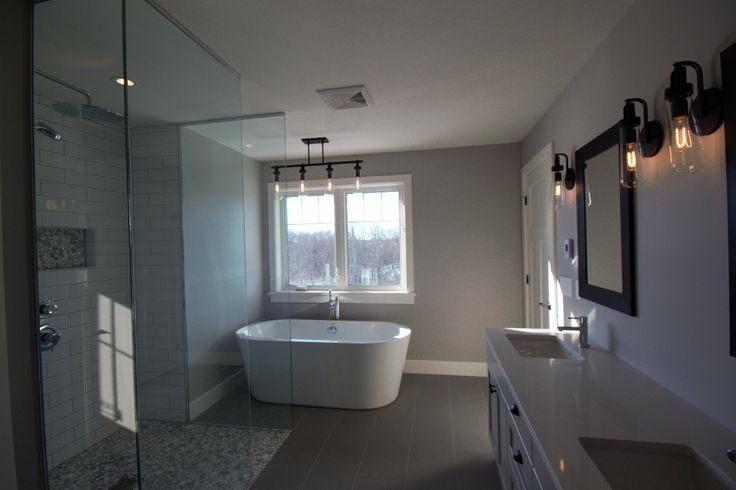 Master bathroom with zero transition tiled glass shower, freestanding tub and quartz counter tops.