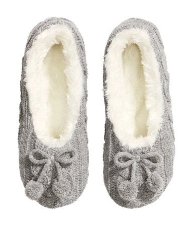 Cable-knit slippers with soft soles, a pile lining and a decorative bow at the front.