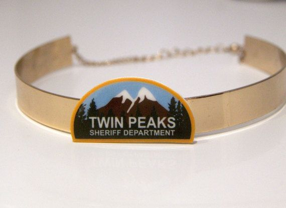 TWIN PEAKS GOLD CHOKER  THE STORY:  David Lycnhs Twin Peaks is coming back to television screens in 2017, and at MITCHUMVSBOGART we are beyond excited!  This choker is a celebration of the Lynch world and the Twin Peaks universe. The Twin Peaks Charm is modelled on the fabric patches part of the Twin Peaks Police Department uniform as seen on the show. MATERIALS:  Brass, gold choker with adjustable chain at the back.
