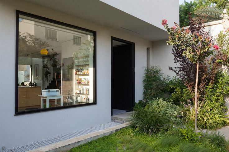 Bílá fasáda domu se střídá v horizontálních pruzích s dominantním prosklením.