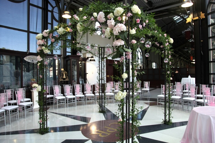 Flower covered gazebo at the Fairmont Palliser CPR Pavilion in Calgary, Alberta. Cream colored hydrangea, pink cymbidium orchids, pink roses, and ivy. Wedding ceremony focal point; silver Chiavari chairs with pink organza chair sashes set up for a ceremony in the round (Photo by M. MacRae)