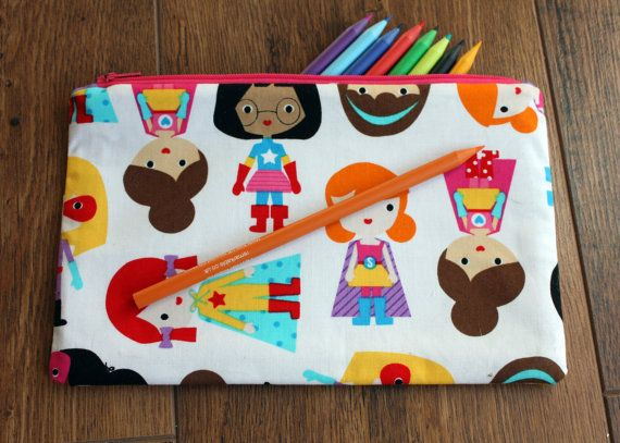 A fun handmade cotton pencil case with cartoon superheroes fabric on the outside and a purple polka dot fabric on the inside and a contrasting pink