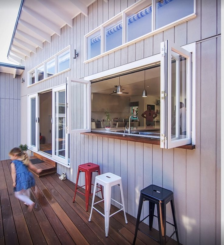 Adjoining indoor and outdoor rooms by adding a bi-fold window is a great way to serve and eat food and drinks outside. Colourful stools make a decorative feature and maintain a simple coastal style.  Photo credit: pinterest.com