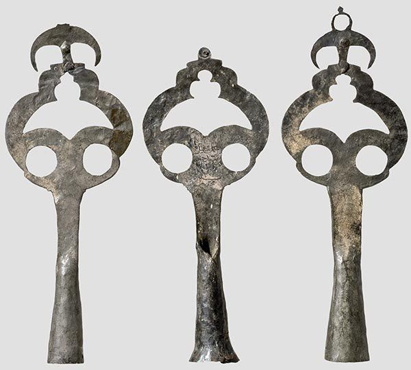 """Ottoman standards for mounting on tent poles, end of the 18th century.  Each is of tinned copper with an openwork banner and a conical socket with two holes. One has an engraved maker's signature and date """"1201"""" (= 1787). Two have incomplete crowns. Heights 56 to 63 cm."""