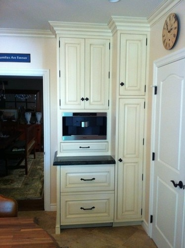 Ivory cabinetry with built-in coffee maker above paneled integrated refrigerator drawers.