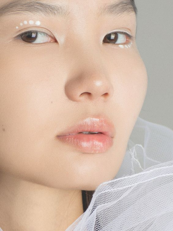 Minimalistic white graphic makeup. Asian beauty in shot by Evgenya Kayumova