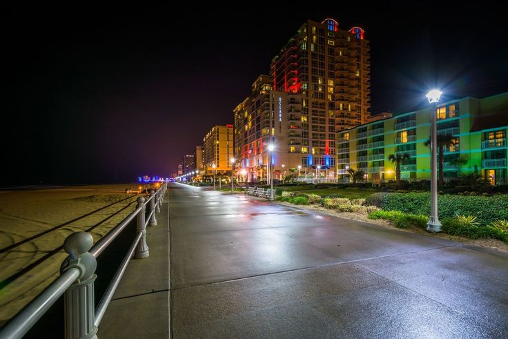 The boardwalk and highrise hotels at night in Virginia Beach, Virginia.