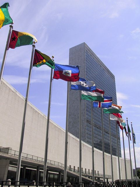 Line of National Flags in front of the UN Headquarters, New York - The United Nations building in Manhattan is one of the most known buildings in NYC. There are tours available but make sure to check their website for exact times and security protocols. (https://www.facebook.com/TravelingWarrior) #UnitedNations #NYC #attractions