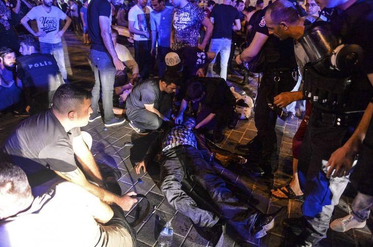 People attend to a man that was protesting against the coup, laying wounded when Turkish forces soldiers opened fire to disperse the crowd, in Istanbul's Taksim square, early Saturday, July 16, 2016