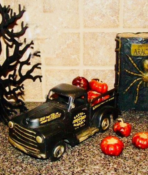 Retro black pickup filled with \u201cpumpkins\u201d for Halloween decor