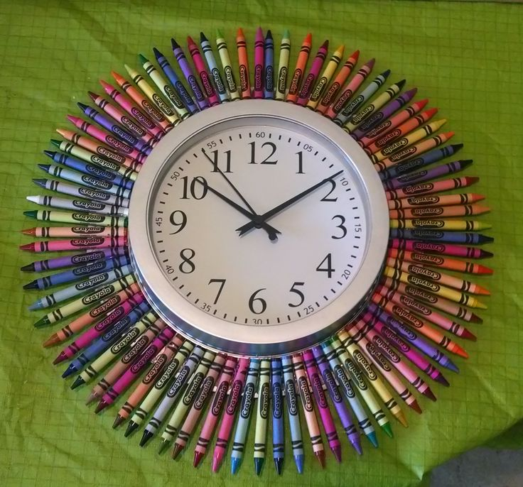 """Super easy crayon clock....cheap $3. clock from Target, box of 96 Crayons, hot glue, silver craft paint & leftover cardboard. Cut a 1"""" & 1/2 larger circle then the clock. Secured the cardboard to the clock with the screws clock came with. Cut a hole in the back for haning & access. Painted the showing trim silver. Attached crayons with hot glue to the cardboard. Quick and Easy!"""