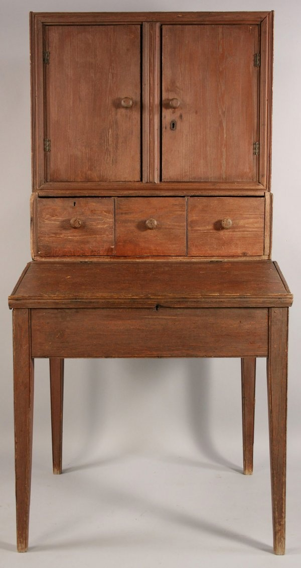 "Johnson Co., Georgia plantation desk with the original red paint over yellow pine. Two pieces comprised of top with two doors over three drawers all with applied molding resting on tapered legs with slant front. Overall good condition with expected wear to painted surface, missing trim on bottom of legs and one corner. 40 1/2"" H x 38 3/8"" W x 33 1/2"" D. 19th century. Provenance: From a private Georgia collection and featured on page 25, April 1997 issue, of ""Early American Homes"" magazine."