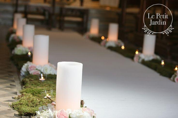 Navata di una chiesa realizzata con muschio, e ghirlande di ortensia bianca e rose Sweet Avalanche.  Candele per rendere l'atmosfera ancora più intima e romantica.